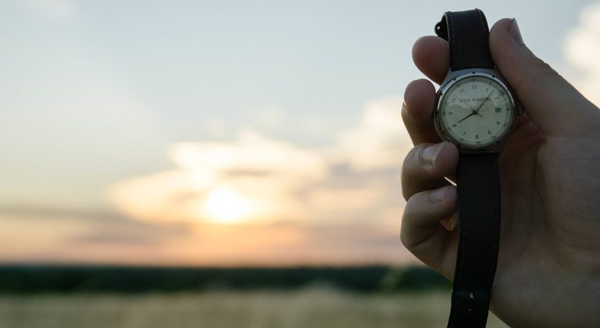 Hand holding a watch up to the horizon