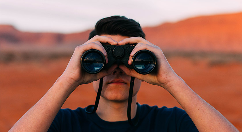 Man looking through binoculars in desert landscape