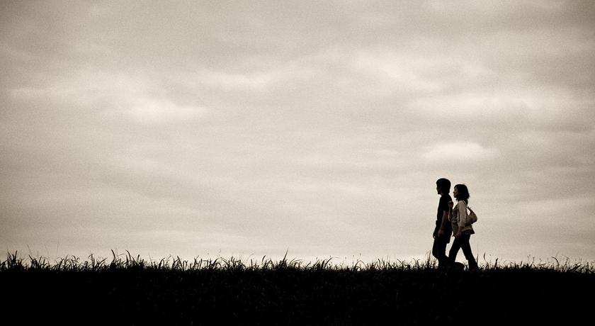 couple walking under grey sky