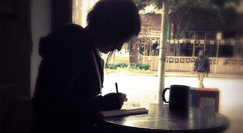 Woman journaling in a cafe