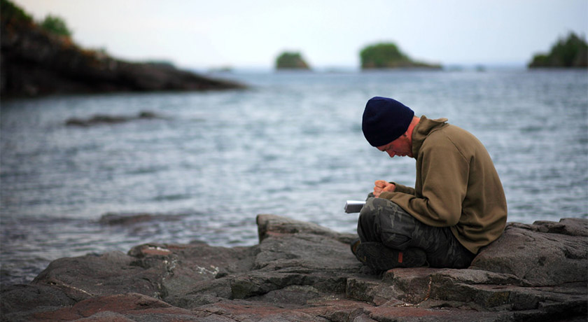 Man journalling by the sea