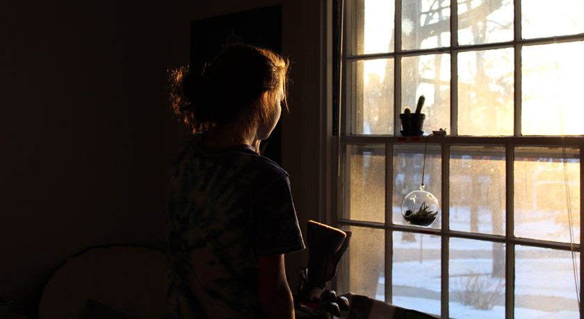 Girl at a window in morning sun