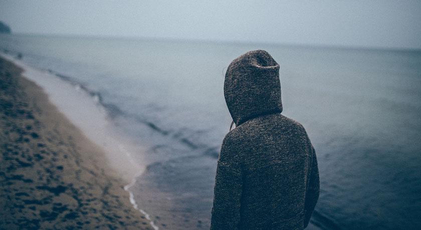 Woman in hoodie walking on beach