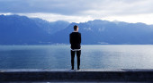Man standing at edge of a lake
