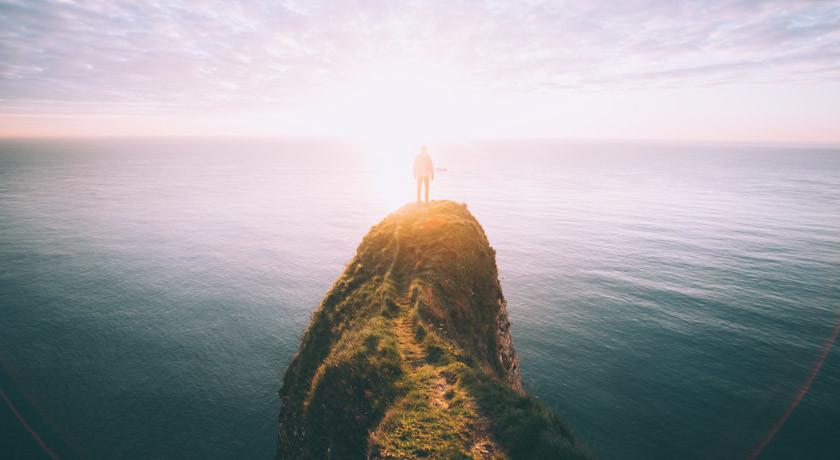 Man standing on headland looking to horizon