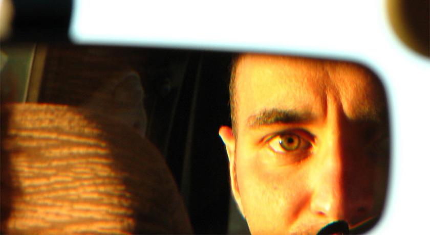 Man looking in rear view mirror