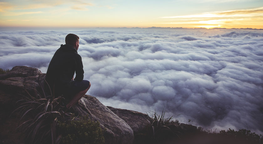 Man sitting above the clouds looking across valley at sunrise