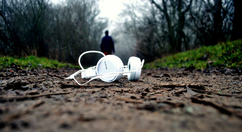 headphones in a forest, person in background