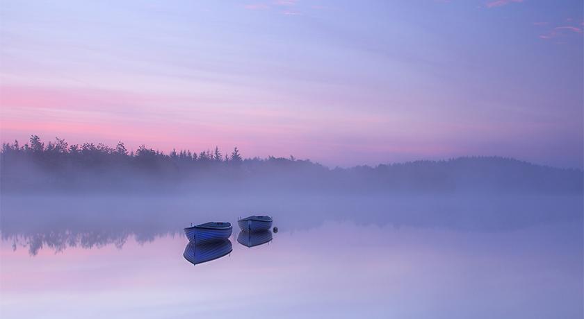 Boats on lake at dawn