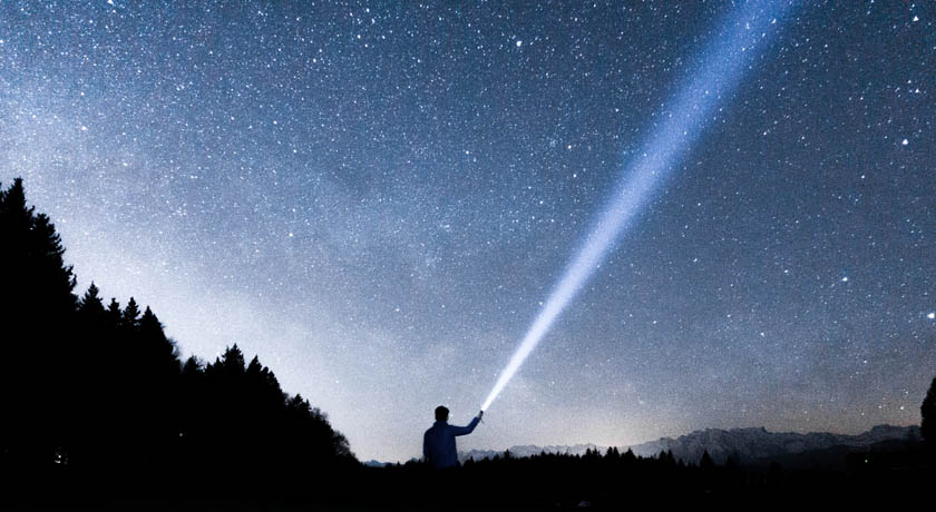 Man searching the night sky with torch
