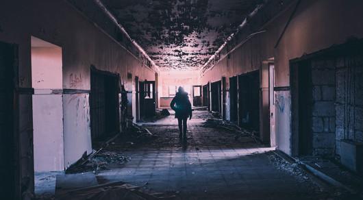 Woman walking through derelict building