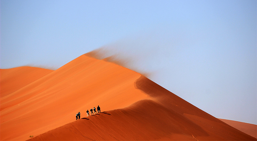 Small group walking on desert sand dunes