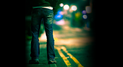 Man standing on a city street at night