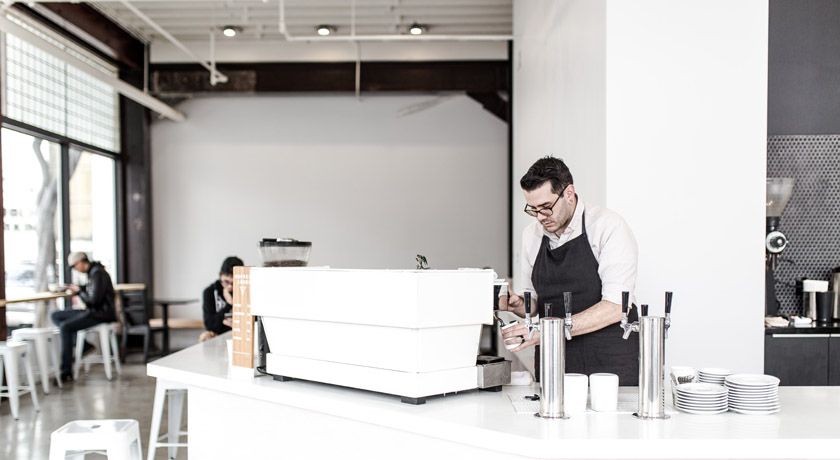 Barista at work in cafe by Tim Wright