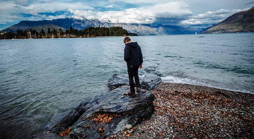 Man at a shoreline looking at the water