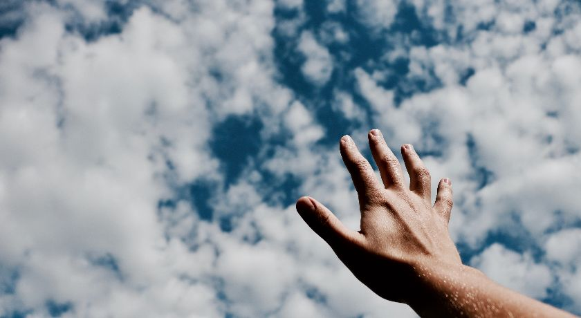 A hand reaching up to the sky